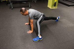 Todd demonstrating alternating leg push up stretch
