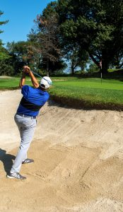Todd performing a back swing in a sand trap